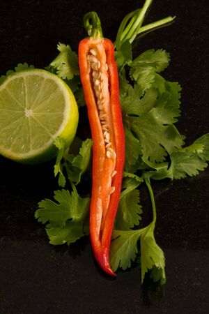 Chilli, coriander and lime garnish on a granite work surface Stock Photo - 4928444