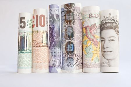 A pile of rolled British Banknotes against a white background photo
