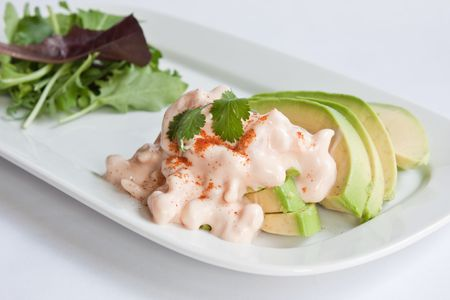 Slices of avocado topped with prawns in a marie rose sauce served with a green salad photo