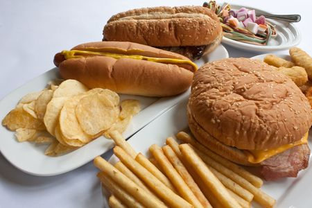 Paltes of junk food including burgers, fries, hot dogs and sweets photo