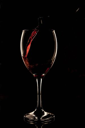 Red wine being poured into a glass photo