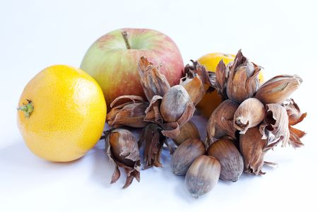 Apple, satsuma and cobb nuts isolated over a white background photo