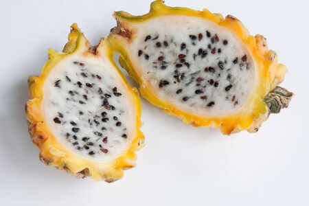 exotic fruits: A yellow dragon fruit halved & isolated against a white background
