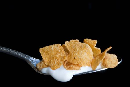 cuiller�e: Une cuiller�e de ma�s en flocons de c�r�ales avec du lait