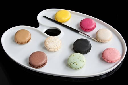 A palette-shaped plate with brightly coloured French macaroons and paintbrush depicting a creative approach to food photo