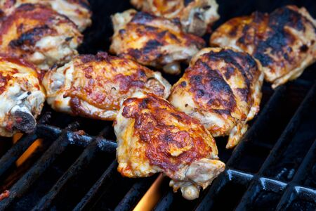 Chicken thighs in a chilli marinade cooked on a barbeque grill photo
