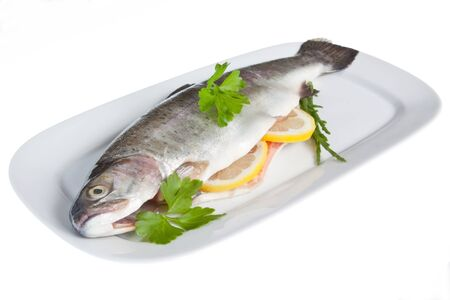 garnish: A rainbow trout prepared for cooking, stuffed with slices of lemon and parsley