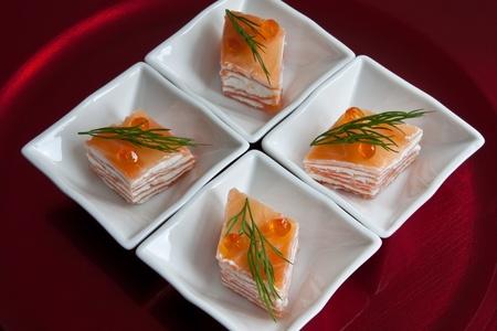 Diamant en forme de portions de couches de fromage à la crème de saumon fumé servi dans plats blancs présentées sur un chargeur de rouge. Garnie avec des oeufs de saumon à l'aneth et