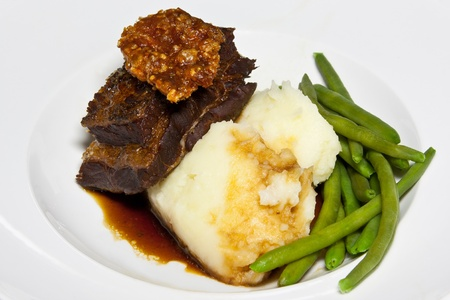 crackling: Braised pork belly garnished with pork crackling served with a rich jus, mashed potatoes and green beans