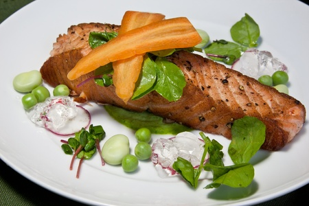 broad leaf: A panfried salmon steak on a pea puree garnished with radish, raw peas, broad beans, micro herbs, pea shoots, sliced carrot & a ginger jelly