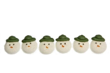 sugarcraft: A row of edible sugarcraft snowmen faces for use as cake decorations