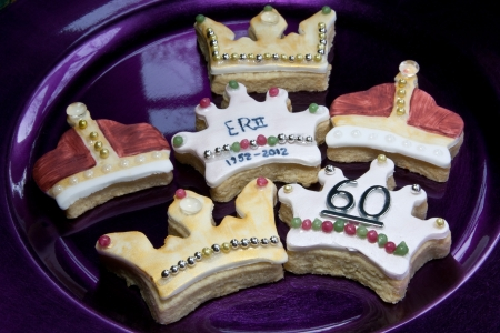 Crown cookies to celebrate the diamond jubilee of Queen Elizabeth II. Decorated with gold & silver dragees, edible diamonds & paint, presented on a purple laquered charger Stock Photo - 12430105
