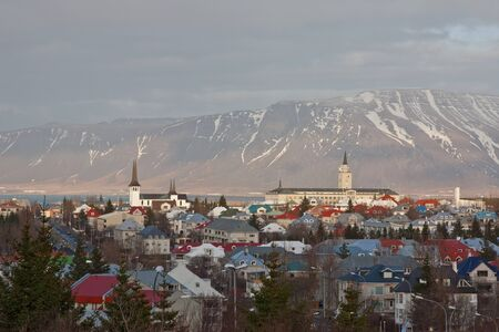 reykjavik: A view of Reykjavik, capital of Iceland, showing buildings, plants & the mountains behind the city