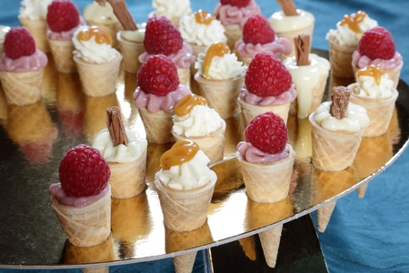 Mini ice cream cones filled with raspberry, lemon   white chocolate mousses topped with chocolate flakes, raspberries   toffee sauce photo
