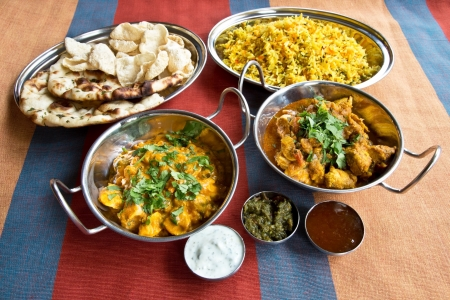 Dishes of curry in Balti dishes with rice, naan bread, poppadoms & a selection of chutneys photo