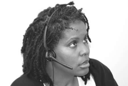 dreads: A Black woman in dreads wearing a headset.
