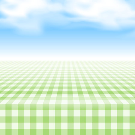 Empty picnic table, covered with checkered gingham tablecloth. Clear blue sky background.