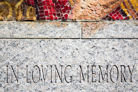 in loving memory: The words In loving memory carved in a granite surface with a small portion of tiled mosaic on top.