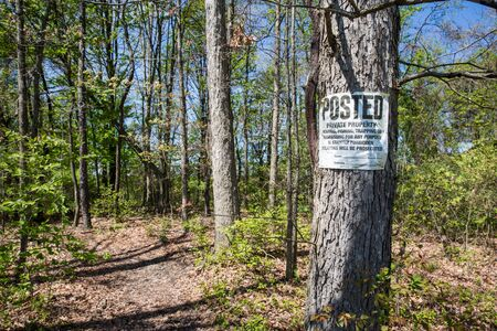 Private property sign posted on tree next to a faint trail through the woods.