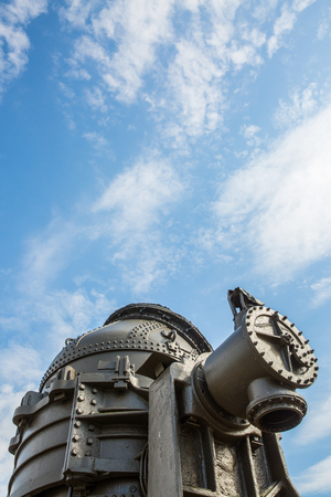 View, from the ground, of upper part of historical Station Square Bessemer converter in Pittsburgh with clouded blue sky filling top two thirds of the frame.
