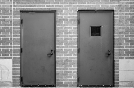 Grayscale symetrical image of two metal doors in a brick wall. The door on the right has a small square window. Stok Fotoğraf