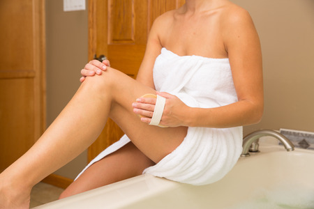 handled: Young woman sitting on side of tub holding handled dry brush to side of her thigh