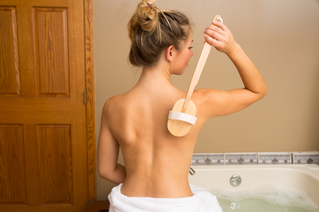 bath: Young woman sitting on edge of bath holding wooden-handle dry brush to her bare back