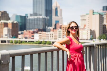 Attractive young woman in pink dress and sunglasses standing in the sun in front of cityscape