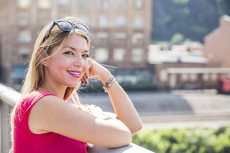 Smiling attractive young woman in pink dress with sunglasses on head leaning against railing in front of large building Stock Photo