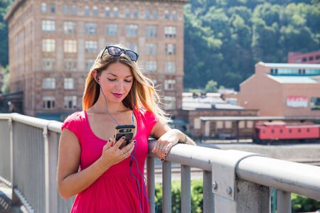 Smiling attractive young woman in pink dress with sunglasses on head holding smartphone listening to ear phones leaning against railing in front of large building