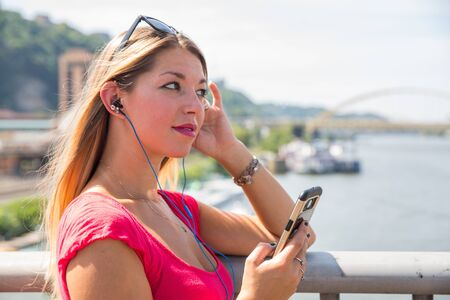 Attractive young woman in pink dress with sunglasses on head holding smartphone listening to ear phones leaning against railing