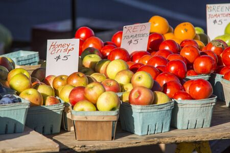 variety of fruit and vegetables in baskets arranged on tables at a farmers market Stock Photo