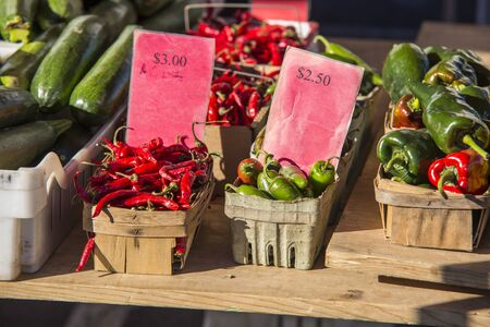 chili peppers, jalapeno peppers, and poblano peppers in baskets on a table at a farmers market Stock Photo