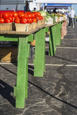 tomatoes and a variety of vegetables in baskets arranged on tables at a farmers market
