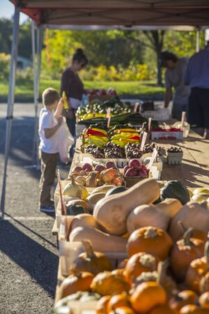 tables with fruit and vegetables at a farmers market with a child blurred in the background holding a pepper Stock Photo