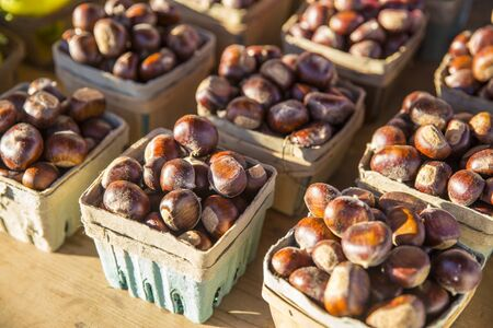 baskets of chestnuts arranged as on a table at a farmers market