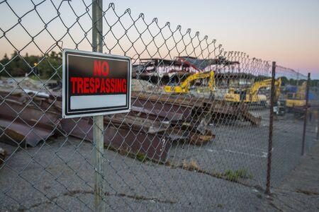 prohibido el paso: ninguna muestra de violación en una valla de tela metálica en la parte delantera de una obra de construcción borrosa en la oscuridad