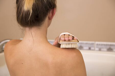 dry brush: Bare back shoulders of young woman holding dry brush to top of her right shoulder