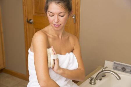 dry brush: Attractive young woman in white towel in bathroom holding dry brush to her upper arm