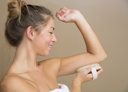 dry brush: Attractive young woman in white towel holding dry brush to under side of upper arm