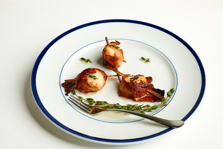 Skewered Bacon Wrapped Scallops with Thyme and drizzled melted butter on a blue rim plate with a white background