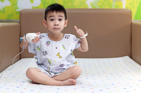 Sick child patient thumb up with bandage cover hand and saline solution sit on bed of colorful dots feeling better healthy by good nursing care of hospital and medical treatment fee pay by life insurance company