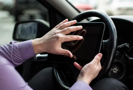 Ein Mann sitzt in einem Auto und arbeitet an einem Tablet PC