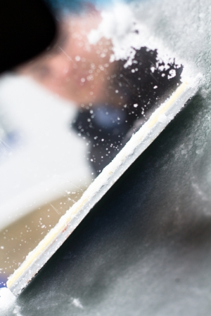 A man scrapes the snow with ice on the windshield of his car photo