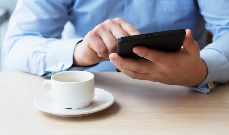 business men: Businessman in a cafe drinking coffee and working on a Tablet PC