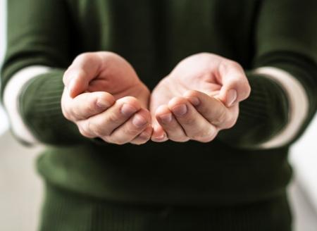get help: A man holds a handful, hands together, asks