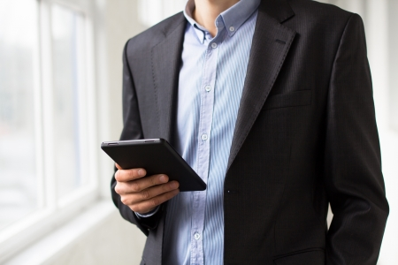Businessman using tablet pc and works on it Stock Photo - 18298309
