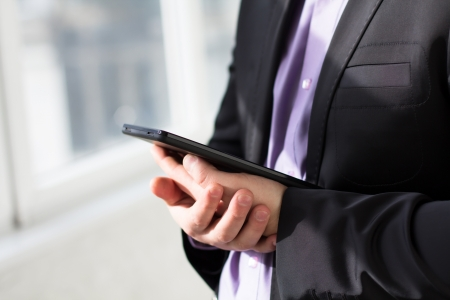Businessman using tablet pc and works on it Stock Photo - 18298179