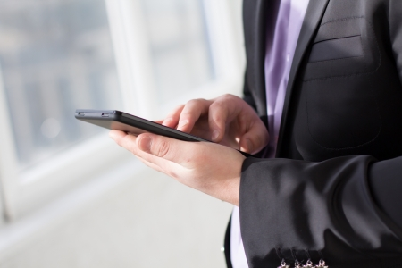 Businessman using tablet pc and works on it Stock Photo - 18298077