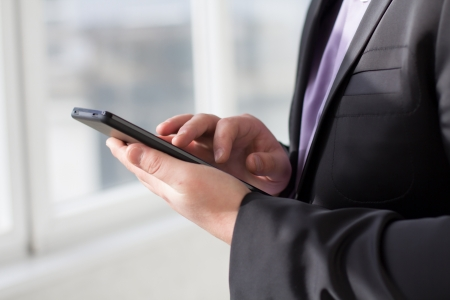 Businessman using tablet pc and works on it Stock Photo - 18298051